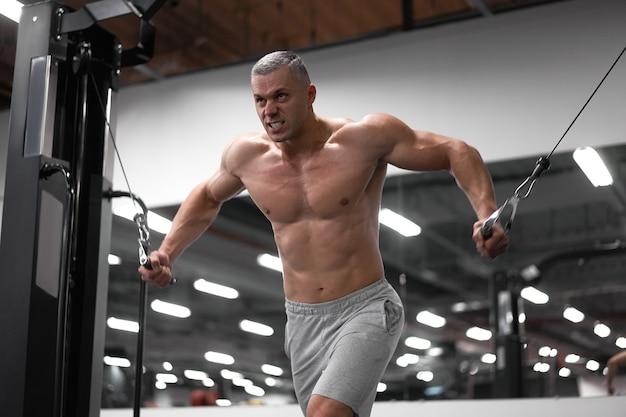 Muscoloso bodybuilder atletico in piedi allenamento petto e spalle muscoli su attrezzature per il fitness