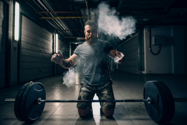Muscoloso uomo barbuto caucasico attraente in ginocchio, guardando in basso, sfarinamento e battendo le mani.
