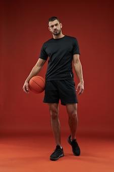 Giocatore di pallacanestro muscolare che guarda e che posa alla macchina fotografica isolata nel fondo rosso
