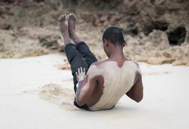 Uomo nero muscolare che ha allenamento in spiaggia tropicale