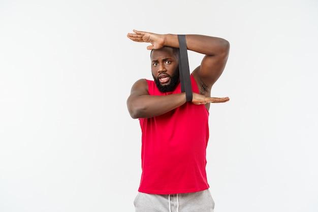 Giovane nero muscolare che si esercita con le fasce elastiche in studio, isolato su bianco.