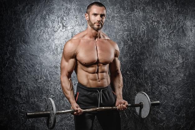 Culturista muscolare che si esercita con un bilanciere