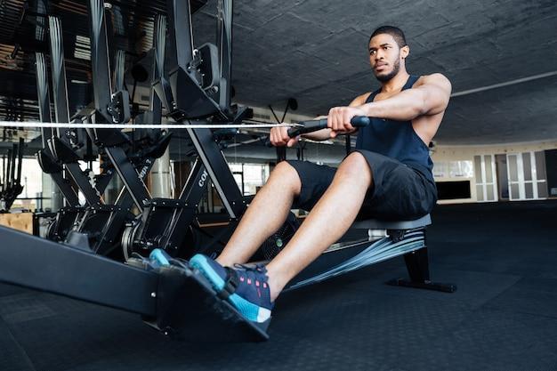 Uomo muscoloso che usa il vogatore in palestra