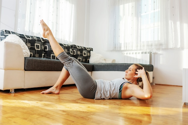 Sportiva in forma muscolare che fa gli scricchiolii sul pavimento a casa durante il blocco.
