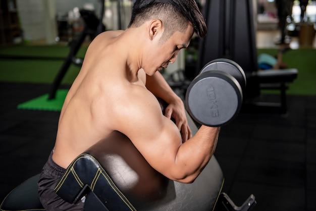 Culturista uomo fitness muscolare è allenamento con manubri in palestra