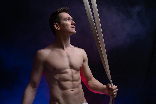 Artista di circo maschio muscoloso con cinghie aeree su sfondo nero e affumicato