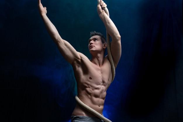 Artista di circo maschio muscoloso con cord lisse su fondo nero e affumicato