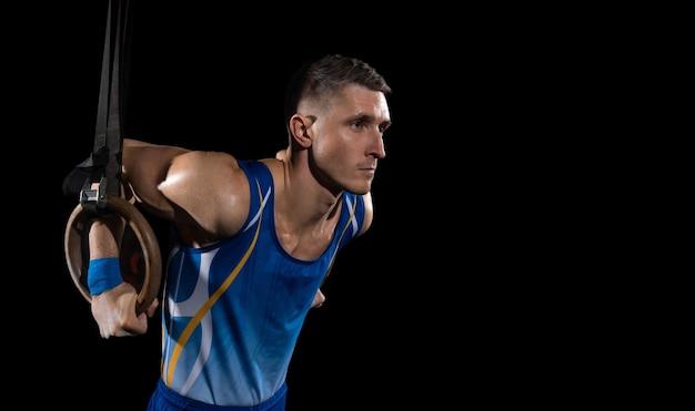 Ginnasta maschio muscolare che si allena in palestra atleta di tipo caucasico flessibile e attivo in blu
