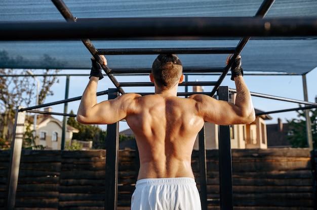 L'uomo muscoloso fa esercizi di pull-up su una barra orizzontale, allenamento in strada