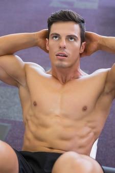 Uomo muscolare che fa gli scricchiolii addominali in palestra
