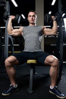 Uomo muscolare che fa pressa sopraelevata con manubri in palestra.