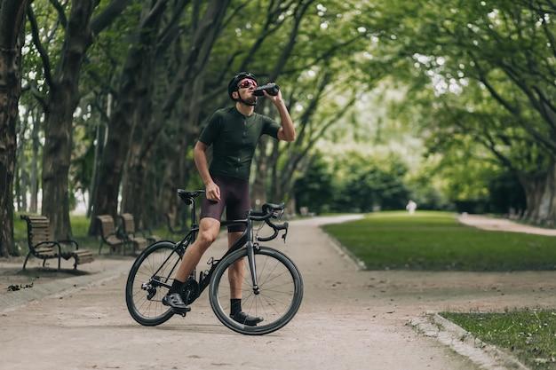 Uomo muscoloso che beve acqua dopo la mattinata in bicicletta al parco