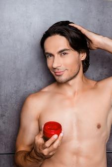 Uomo muscolare che tiene un barattolo di gel per capelli e acconciatura