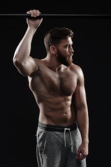 Uomo muscoloso vicino alla barra orizzontale. guardando lontano. sfondo scuro isolato