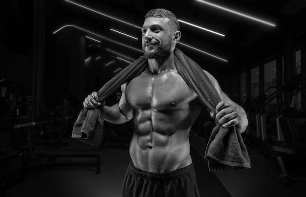Uomo muscoloso in posa in palestra con un asciugamano sulle spalle. concetto di fitness.