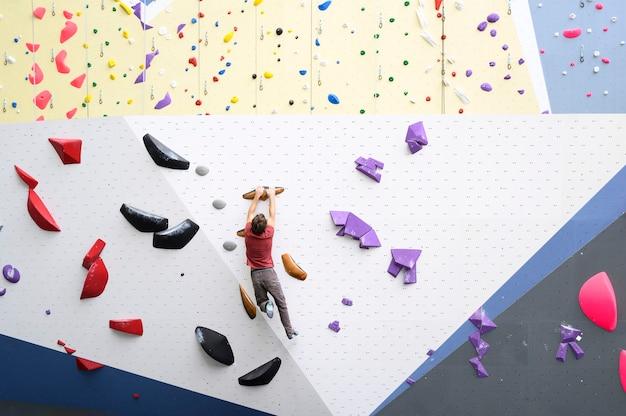 Uomo muscolare che pratica l'arrampicata su una parete di roccia al chiuso