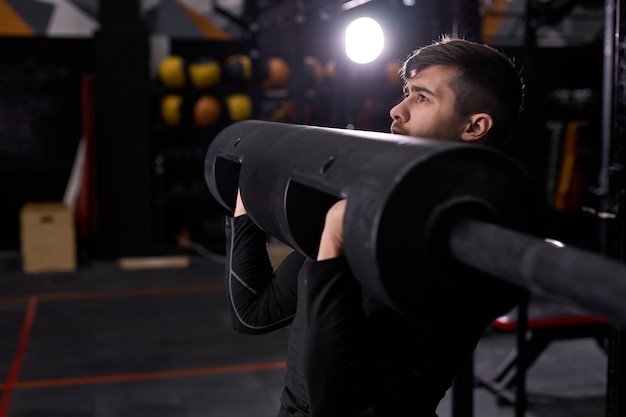 Uomo muscoloso che solleva pesi pesanti, allenamento pompando i muscoli delle braccia. uomo forte utilizzando attrezzature sportive nel moderno centro fitness, palestra. maschio che indossa abbigliamento sportivo, concentrato sull'allenamento