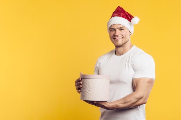 Uomo muscoloso in cappello di babbo natale e scatola attuale in camicia bianca, in piedi sopra il muro giallo isolato
