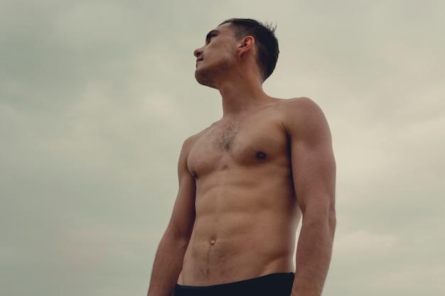 Uomo muscolare che sta sulla spiaggia in uno speedo.
