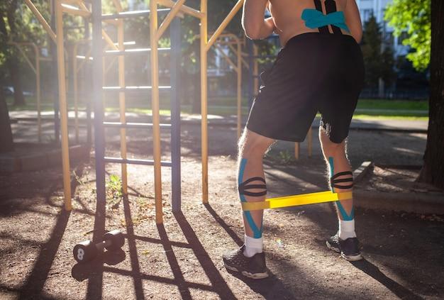 Uomo muscolare formazione fascia di resistenza fitness sulle gambe al campo sportivo. vista posteriore di un giovane bodybuilder irriconoscibile con nastro kinesiologico elastico sull'allenamento del corpo all'aperto. concetto di riabilitazione.