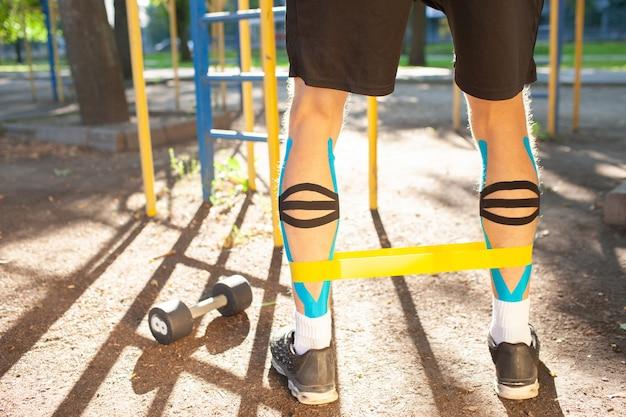 Banda di resistenza fitness allenamento uomo muscolare sulle gambe al campo sportivo