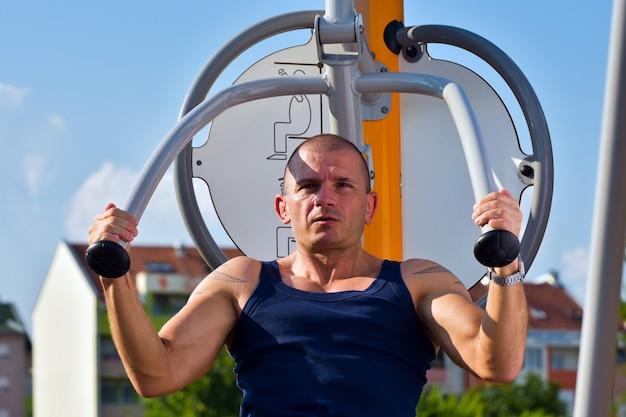 L'uomo muscoloso in canottiera si esercita all'aperto sull'attrezzatura.
