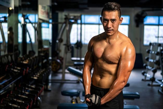 Uomo muscoloso che indossa abbigliamento sportivo a corpo libero facendo esercizio per allenamento bodybuilding in palestra