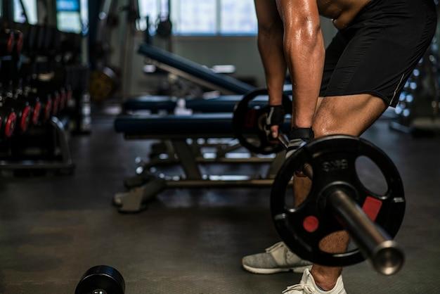 Uomo muscoloso che indossa abbigliamento sportivo bilanciere di sollevamento a corpo libero per allenamento bodybuilding in palestra