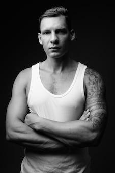 Canottiera sportiva bianca d'uso dell'uomo muscolare contro la parete nera