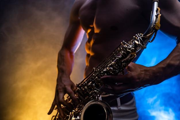 Uomo muscoloso con il torso nudo che gioca sul sassofono con fumo