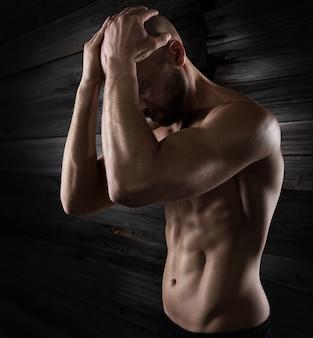 Uomo muscoloso con vestibilità perfetta sulla parete del grunge