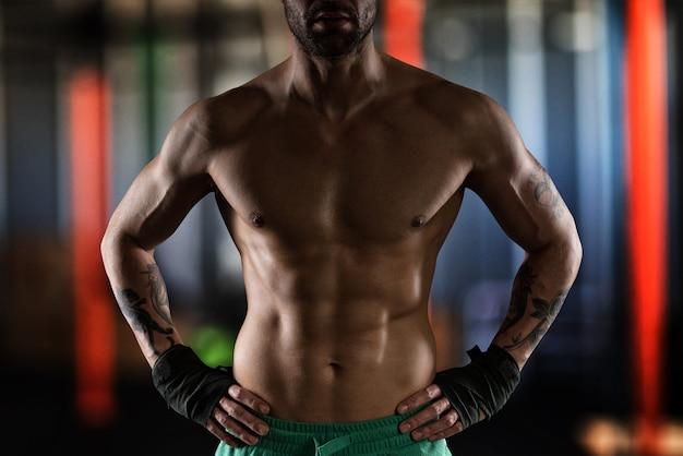 Uomo muscoloso con vestibilità perfetta e nastri nelle sue mani
