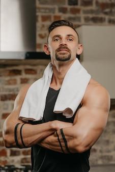 Un uomo muscoloso con un asciugamano bianco sulle spalle posa con le braccia conserte sul petto nel suo appartamento