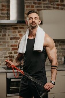 Un uomo muscoloso con un asciugamano bianco sulle spalle posa con la corda elastica nel suo appartamento