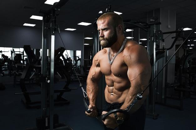 Uomo muscolare che risolve in palestra che fa le esercitazioni al tricipite
