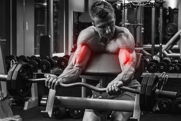 Uomo muscolare che si allena con un bilanciere. specializzazione per bicipiti nel bodybuilding.