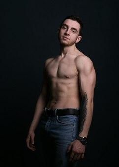Il modello muscolare mette in mostra il giovane sulla superficie scura. foto verticale