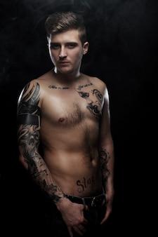 Uomo muscoloso sexy con tatuaggio su sfondo scuro