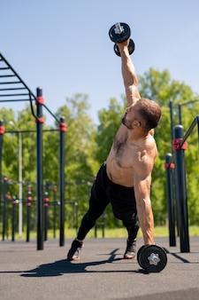 Ragazzo muscoloso a torso nudo che alza un braccio con un bilanciere pesante mentre si appoggia sulle gambe e un altro braccio durante l'allenamento all'aperto