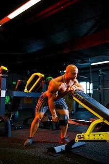 Uomo senza camicia muscolare che fa esercizi con manubri come parte del suo allenamento di bodybuilding. motivazione per il fitness, stile di vita sportivo, salute, corpo atletico, corpo positivo