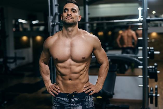 Uomo senza camicia muscolare con le mani sulle anche che posano in una palestra