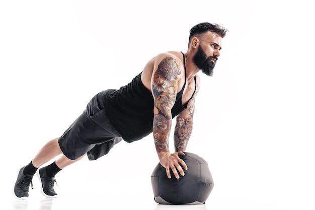 Muscoloso tatuato maschio barbuto esercizio fitness pesi palla medica push up esercizi isolato sul muro bianco.