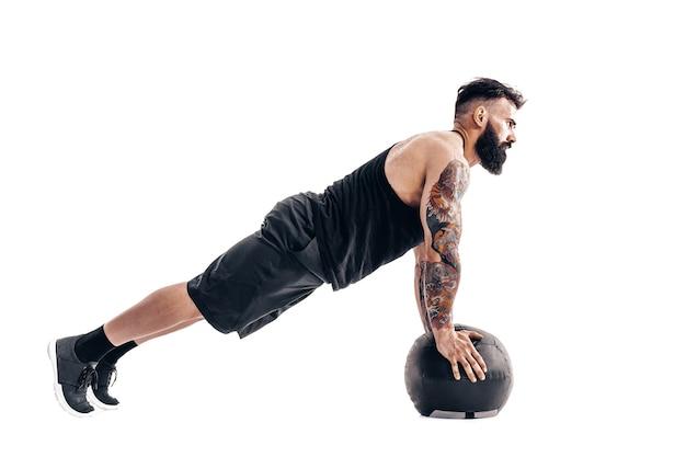 Muscoloso uomo barbuto tatuato che esercita i pesi di forma fisica esercizi di push up della palla medica