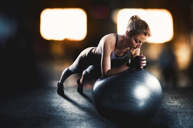 Donna muscolare su una palla fitness con biancheria intima sportiva in palestra