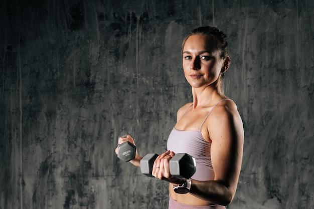 Giovane donna atletica muscolare con un bel corpo perfetto in abbigliamento sportivo che tiene il manubrio durante l'allenamento con i pesi. femmina caucasica fitness in posa in studio con sfondo scuro.