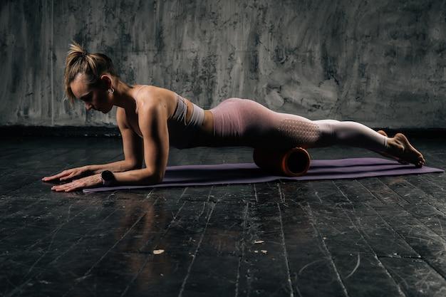 Giovane donna atletica muscolare con un bel corpo perfetto in abbigliamento sportivo che massaggia gambe e fianchi, usando il rullo fitness e facendo la tavola sdraiata sul tappetino da yoga. femmina caucasica di forma fisica che posa nello studio.