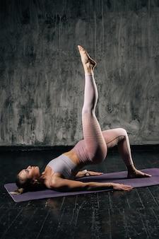 Muscolare giovane donna atletica con perfetto bel corpo indossando abbigliamento sportivo facendo allenamento alzando le gambe sdraiato sul tappetino da yoga. femmina caucasica fitness in posa in studio con sfondo grigio scuro.