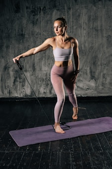 Giovane donna atletica muscolare con un bel corpo perfetto che indossa abiti sportivi che si esercitano con elastico di resistenza. addestramento femminile caucasico di forma fisica con l'espansore d'allungamento in studio.