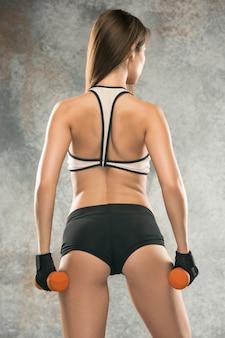 Muscoloso giovane atleta femminile su sfondo grigio. donna caucasica con corpo in forma in posa fiducioso. concetto di stile di vita sano, bellezza, sport, perdita di peso e dieta. fitness. esercitati con i pesi.