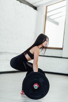 Donna giovane muscolare di forma fisica che solleva un crossfit di peso in palestra